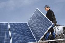 Ein Solarteur montiert Solarmodule zu einer PV-Anlage